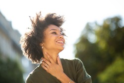 Close up portrait beautiful young black woman smiling outdoors and looking away