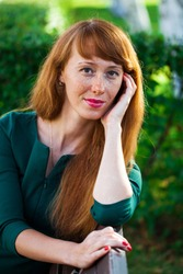 Close up portrait beautiful young red hair woman posing on summer park
