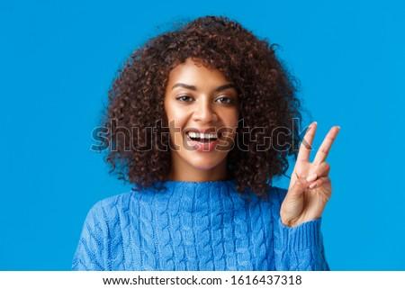 Close-up portrait carefree, happy joyful woman celebrating holidays, wishing everyone good new year, showing peace sign and smiling joyfully, express posivity and joy, wearing sweater
