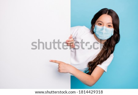Close-up portrait cheerful cheery wavy-haired girl demonstrating empty space ad advert point finger covid outbreak news wear medical mask isolated bright shine blue color background