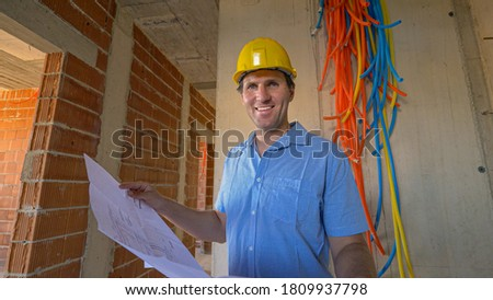 CLOSE UP, PORTRAIT: Cheerful contractor smiles after examining installations and comparing them to the floor plans he holds in his hands. Young Caucasian male smiling while holding house blueprints. stock photo