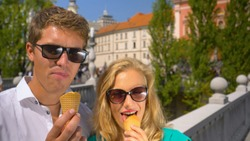 CLOSE UP, PORTRAIT, COPY SPACE: Joyful Caucasian couple enjoys eating ice cream in the sunny streets of Ljubljana. Man and woman travelling across Slovenia eating tasty ice cream on hot summer day.