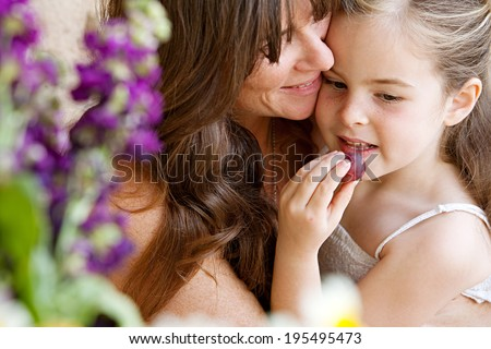 Close up portrait detail of an attractive mother and her young daughter hugging and being close at home with girl eating a fresh natural grape. Loving portrait of family holidays, outdoor lifestyle.