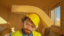 CLOSE UP, PORTRAIT, DOF: Funny shot of a smiling builder getting hit with a thick piece of foam. Bearded male surveyor wearing a yellow helmet gets struck in the head by a piece of falling insulation.