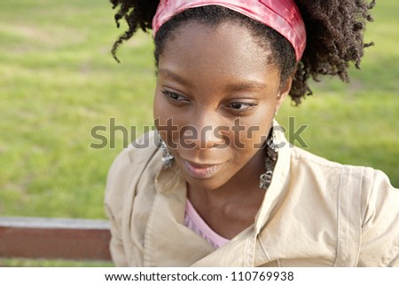 Close up portrait f a young black woman sitting on a bench with green grass in the background, smiling.