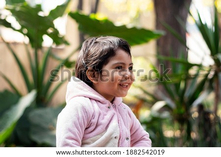 Close up portrait from the side of a little happy latin girl, smiling in the garden with green plants at the background. Foto stock ©