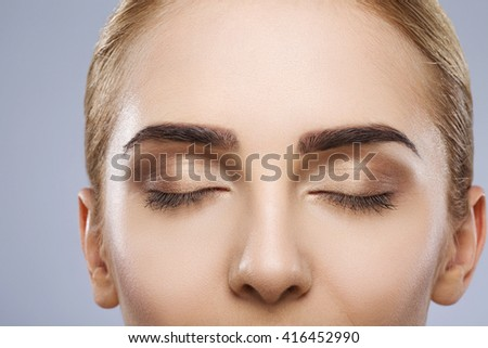 Close up portrait girl with fixed hair behind, nude make up, closed eyes and thick eyebrows, beauty photo, make up model, portrait, close up, copy space.