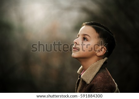 Close up portrait, handsome boy looking up surrounded by warm colors, outdoor portrait