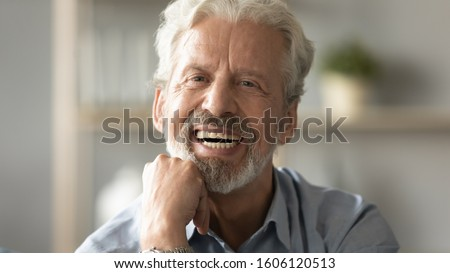 Close up portrait handsome face of 60s elderly man having candid wide toothy smile put fist under chin looking at camera concept of healthy person enjoy retired life, dentures services for old people