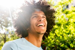 Close up portrait handsome young North African man with afro hair laughing outside