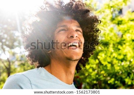 Close up portrait handsome young North African man with afro hair laughing outside  ストックフォト ©