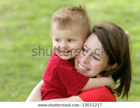 close up portrait headshot of a mother and son smiling and hugging each other looking off camera