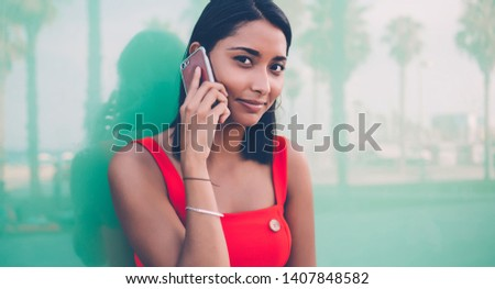 Close up portrait if attractive Latin hipster girl looking at camera while making international mobile conversation, young millennial phoning via contact application while posing near publicity area