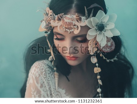 Photo of  Close-up portrait - makeup of a river nymph, in gentle green, yellow, peach hues. The brunette girl with an unusual wreath with seashells. Puppet's baby face. Background thick fog.