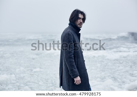 6d9b6392ddb Close up portrait Man in a gray coat walking on the sea.winter vacations