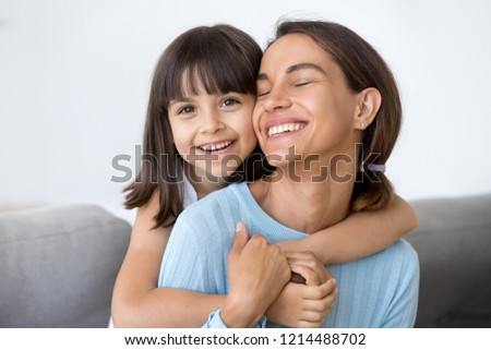 Close up portrait mom and daughter sitting on sofa at home. Mixed race mum with closed eyes smiling her child embrace her piggyback looking at camera. Happy mothers day new parent for adopted kid conc
