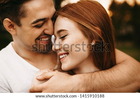 Close up portrait of a amazing young female with red hair and freckles smiling with closed eyes while being embraced from back by her boyfriend closely outside. #1415910188