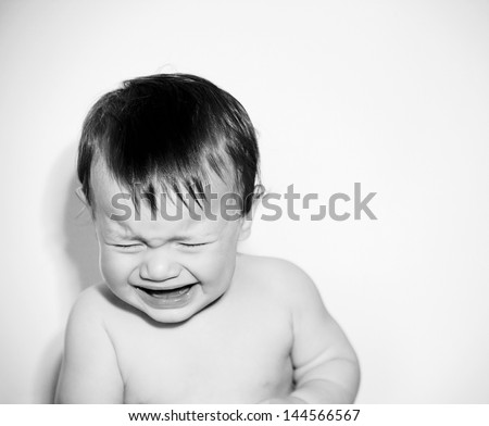 Close up portrait of a baby boy with being unhappy and crying against a white background with a retro style.
