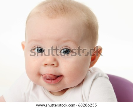 Close up portrait of a baby with tongue sticking out