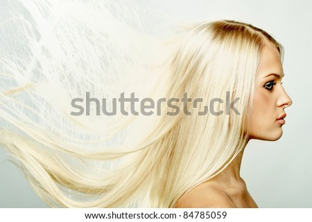 Close up portrait of a beautiful blond female with hair fluttering in the wind