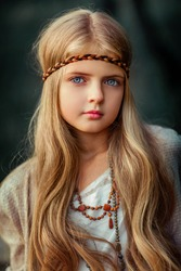 Close up Portrait of a Beautiful blonde girl with blue eyes in a white vintage dress and fashion accessories .Young model posing in a bohemian style. Pretty child looking at camera
