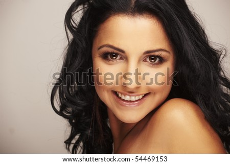Close-up portrait of a beautiful brunett model in studio on light background - stock photo