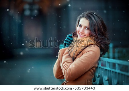 Close up portrait of a beautiful brunette smiling girl in beige fur coat and leather gloves having fun outdoor in town under snowflakes.Pretty young model  looking at camera. Art photo.