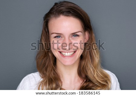 Close up portrait of a beautiful caucasian young woman smiling on gray background