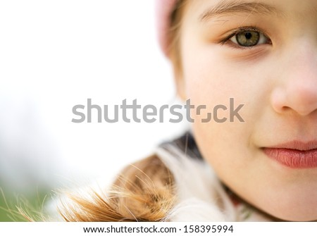 Close up portrait of a beautiful child girl half face in a park looking at camera and being thoughtful during a cold winter day, wearing a warm coat and a pink hat, outdoors.