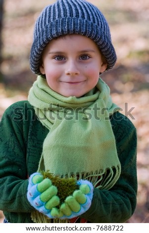Close up portrait of a beautiful child holding a handful of green moss