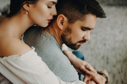 Close up portrait of a beautiful couple sitting on a red chair where woman is whispering loving words to his boyfriend ear.