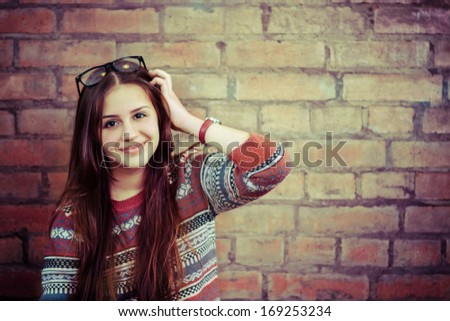 Close up portrait of a beautiful cute teen girl smiling near the brick wall