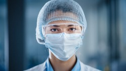 Close Up Portrait of a Beautiful Female Doctor or Surgeon Wearing a Protective Face Mask, Goggles and Disposable Surgical Cap. Laboratory Scientist Calmly Looking at Camera. Covid-19 Pandemic Concept.