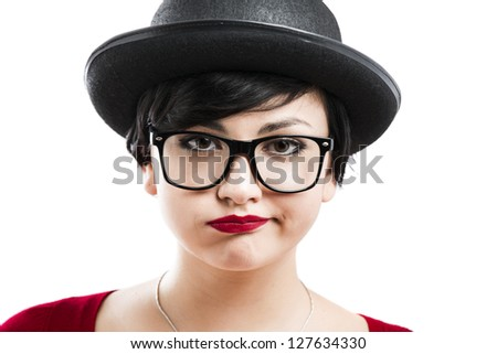 Close-up portrait of a beautiful girl bored with something, wearing a hat and nerd glasses