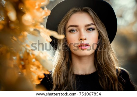 Stock Photo Close up portrait of a Beautiful girl in a dark dress and black hat standing near colorful autumn leaves. Art work of romantic woman .Pretty tenderness model looking at camera.