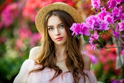 Close up portrait of a Beautiful girl in a pink vintage dress and straw hat standing near colorful flowers. Art work of romantic woman .Pretty tenderness model looking at camera.