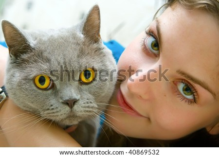 close-up portrait of a beautiful girl with green eyes holding british cat