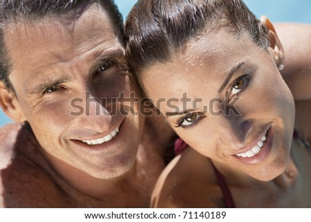 Close up portrait of a beautiful happy man and woman couple in a sun bathed swimming pool smiling with perfect teeth.