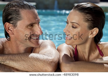 Close up portrait of a beautiful happy man and woman couple looking at each other and resting on their hands at the side of a sun bathed swimming pool smiling with perfect teeth.