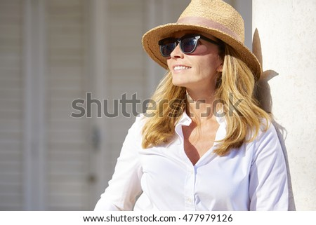 Close-up portrait of a beautiful middle aged lady enjoying a summer day outdoor. #477979126