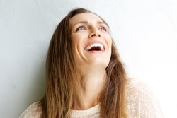 Close up portrait of a beautiful middle aged woman laughing against white background