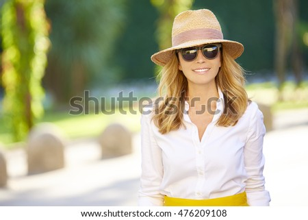 Close-up portrait of a beautiful middle aged woman with straw hat and sunglasses enjoying a perfect summer day. #476209108