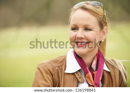Close up portrait of a beautiful older woman smiling and enjoying life outdoors