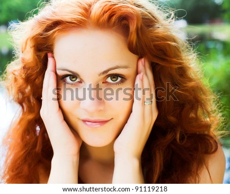 Close-up portrait of a beautiful red-headed girl posing near the lake