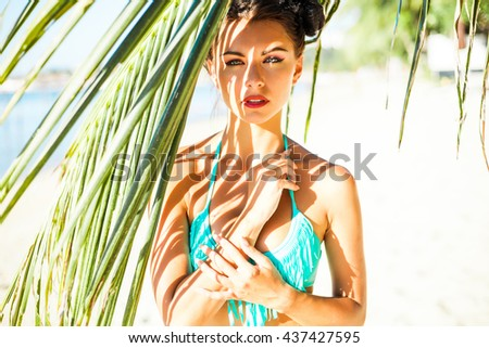 close-up portrait of a beautiful sexy amazing luxurious brunette with blue eyes girl standing under a palm tree on the beach, relaxing on a tropical island, makeup and hairstyle with horns, fashion