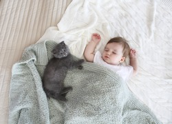 Close up portrait of a beautiful sleeping baby and kitten