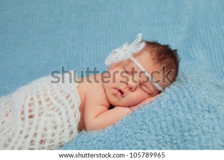 Close-up portrait of a beautiful sleeping baby on blue.0-7 deys baby. New born baby. Soft focus.