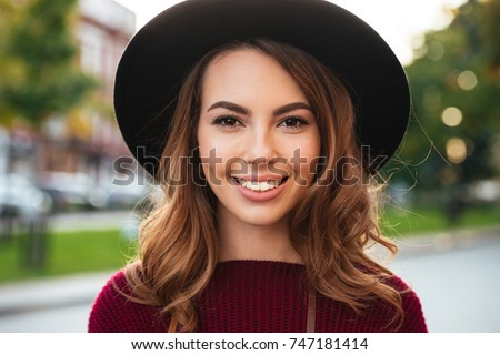 Close up portrait of a beautiful smiling girl with brown hair wearing a hat and looking at camera outdoors