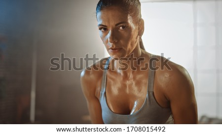Close Up Portrait of a Beautiful Strong Fit Brunette Looking at the Camera in a Loft Industrial Gym with Motivational Posters. She's Catching Her Breath after Intense Fitness Training Workout. Photo stock ©