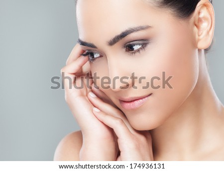 Close-up portrait of a beautiful young black eyed woman holding hands by her face and looking to the side.